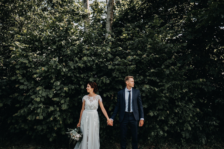 alyvų krūmas jaunieji kostiumas suknelė nuotaka puokštė fotosesija vestuvės fotografas susikibę už rankų