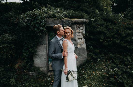 jaunieji santuoka vijokliai fotografas lapai siena akmenys puokštė nuotaka kostiumas suknelė boho rustic fotosesija sodas