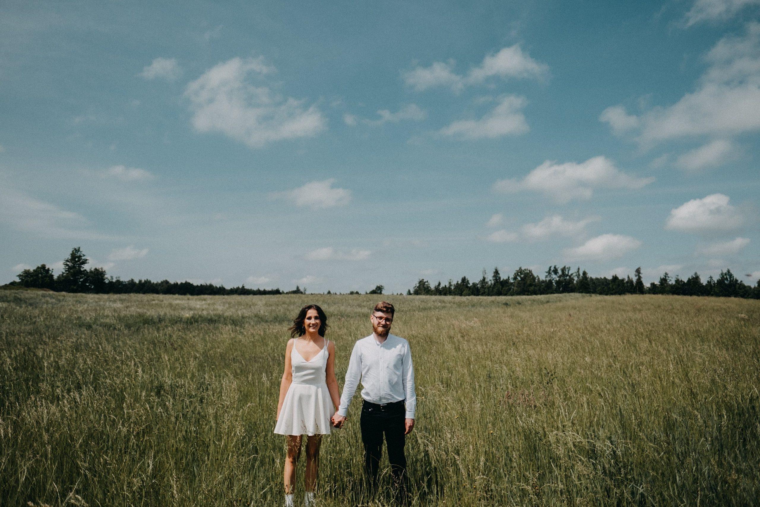 vestuvės jaunieji pieva rustic trumpa suknelė vintage kostiumas Vilnius fotografas fotosesija gražiausia geriausias dangus debesys balti