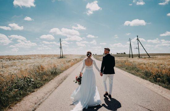 fotografas Kaunas rotušė jaunoji nėriniai suknelė puokštė rustic stilius vestuvės fotosesija laukai kelias dangus gelės žydėjimas jaunikis kostiumas mokasinai baltos kelnės